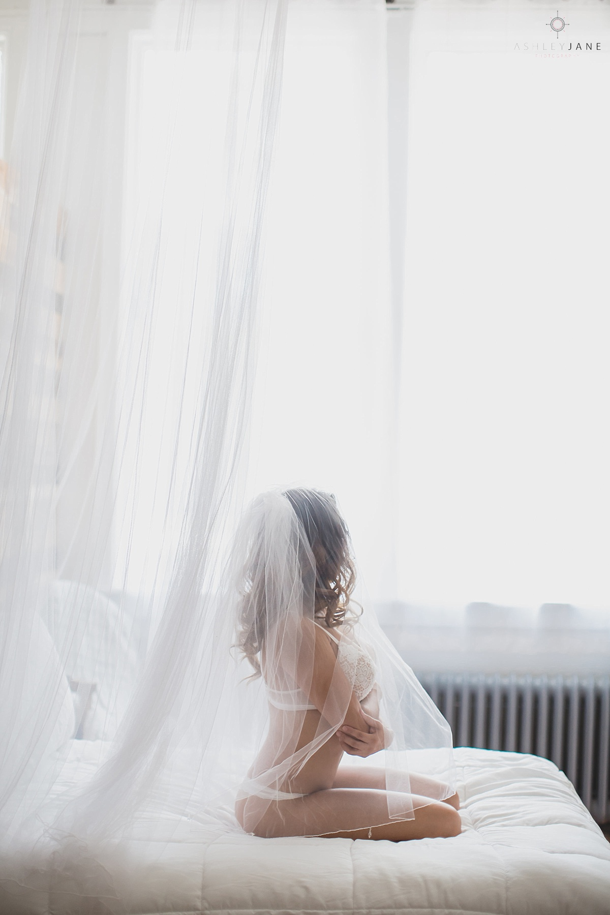 Bride in white lingerie wearing veil sitting on a bed in front of a window. Shot taken at AJP Studios by Orlando Boudoir Photographer.