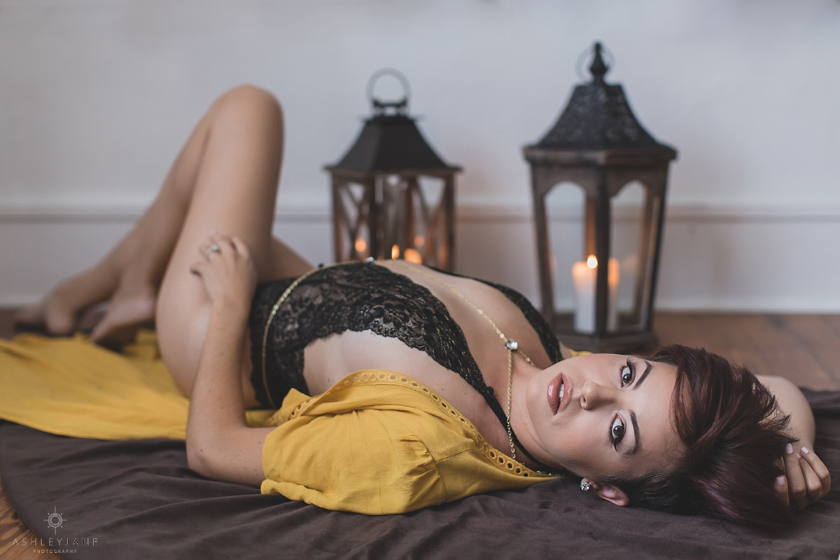 Short red head model in mustard robe and black lace teddy posing for boho styled boudoir shoot by orlando boudoir photographer