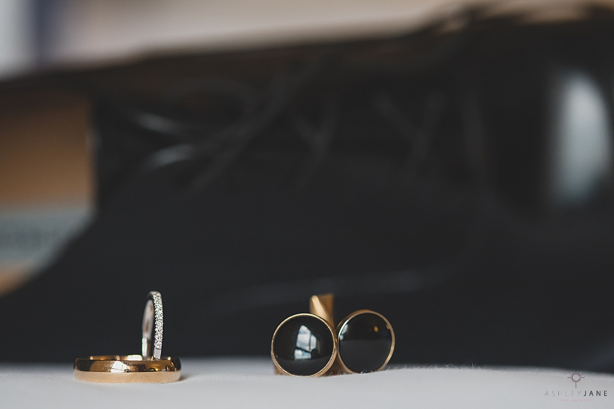 Detail shot of black and gold cufflinks and wedding bands shot by orlando wedding photographer