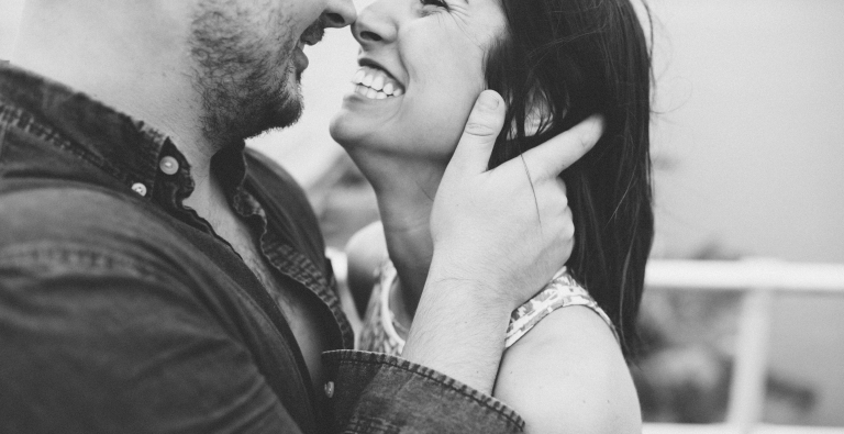 Young couple holding each other close and smiling during engagement shoot in Ponce Inlet. Shot by Orlando Wedding Photographer.