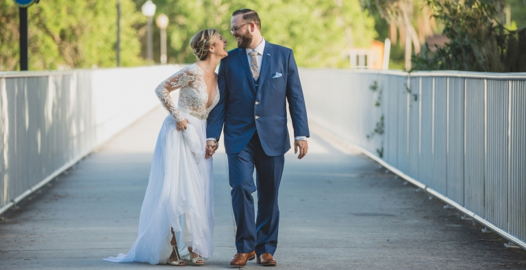 Bride and groom walking across bridge chatting and laughing at Loch Haven Park. Shot by Orlando Wedding Photographer.