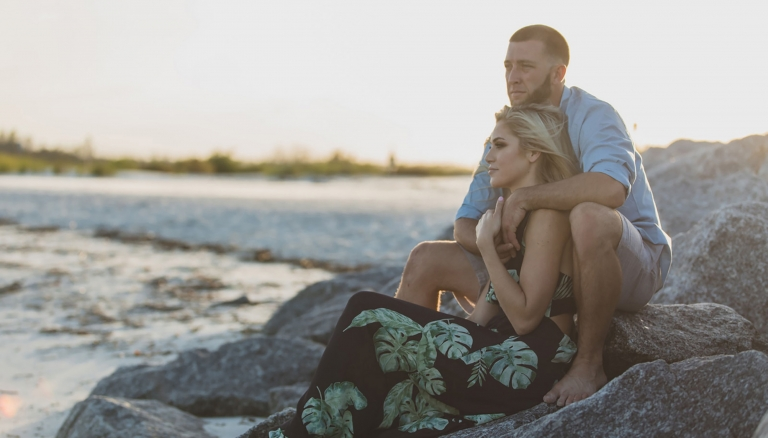 Young couple cuddling on some rocks near the water in Ponce Inlet. Shot by Orlando Wedding Photographer.