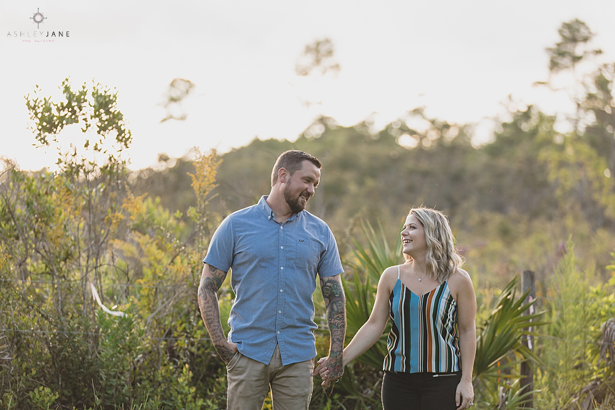Couple holding hands at Wekiwa State Park one of the best engagement session shot by orlando wedding photographer