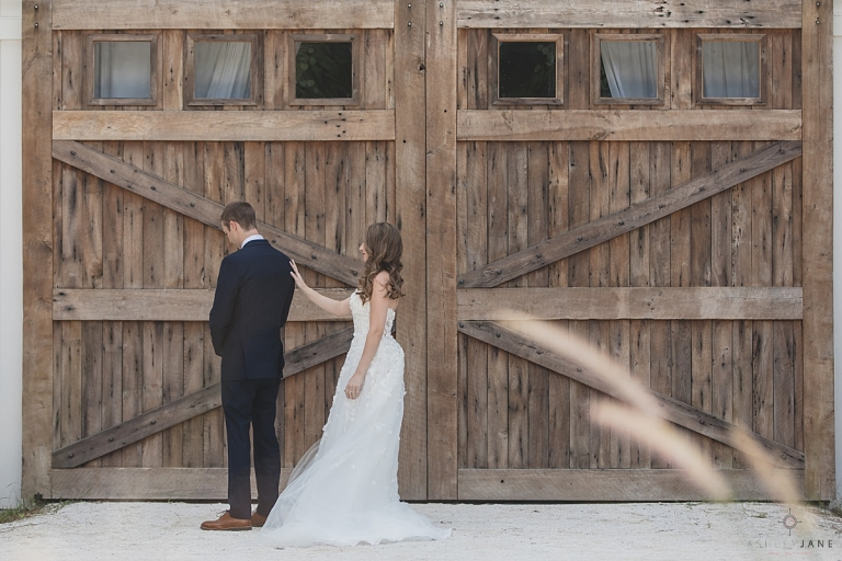 Bride walking up to groom during first look in front of rustic barn doors at the Mulberry in New Smyrna, Florida shot by orlando wedding photographer