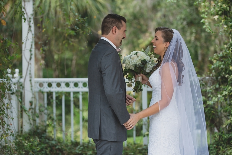Moments after bride and grooms first look at their wedding. Couple is laughing and holding hands under greenery at Lake Mary Events Center shot by Orlando Wedding Photographer.