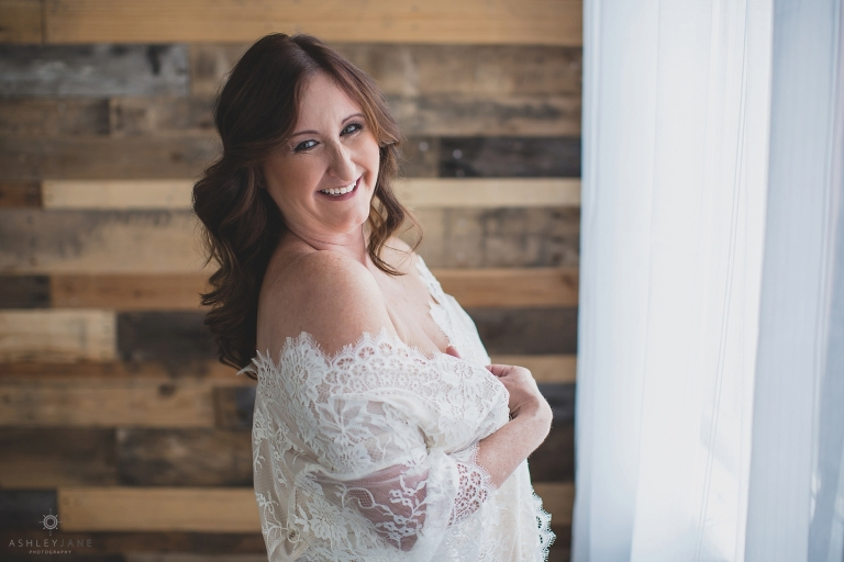 Woman standing with lace robe over her shoulders with a super big happy smile on her face, shot by boudoir photographer in Orlando.