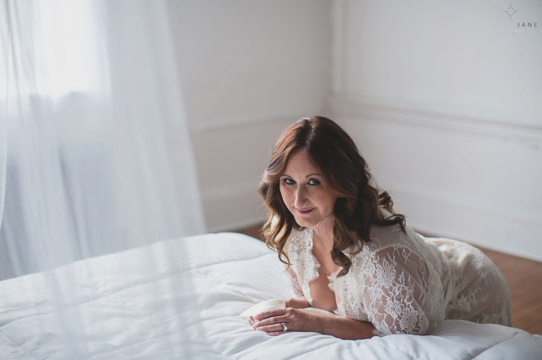 Boudoir image of woman leaning over bed with white lace robe on and canopy in the foreground, shot at sanford Boudoir studio.
